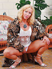 Playful mature blonde on high heels getting naked and spreading her legs