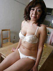 Asian granny Eriko Nishimura taking off her lingerie and toying her hairy gash
