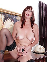 Redhead mature lady in stockings getting naked and toying her shaved gash