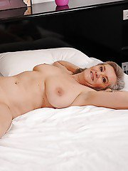 Liberated granny with massive jugs and hairy cooter stripping on the bed