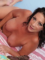 Mature lassie Margo Sullivan stripping and caressing herself on the bed
