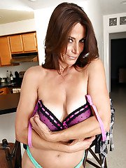 Horny mature brunette stripping and fingering her slit in the kitchen