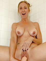 Busty mature blonde takes off her undies and plays with a dildo in the shower