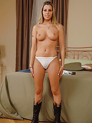 Smiley blonde in jeans and cowgirl boots undressing and spreading her legs
