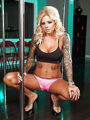 Tattooed striptease dancer slipping off her sexy undies and caressing herself
