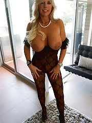 Curvy mature temptress in snazzy nylon suit vibing her gash on the bed