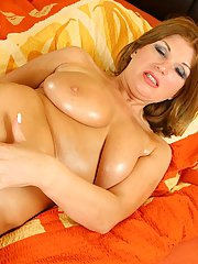 Curvy oiled up MILF playing with her favorite sex toy on the bed