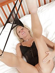 Sassy mature blonde in lingerie taking off her panties and fingering her gash