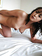Asian MILF Maiko Hirota undressing and posing nude on the bed