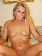 Naughty MILF with shaved gash and piercing in her nipples posing nude