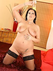 Fatty mature brunette taking off her lingerie and oiling up her massive jugs