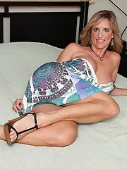 Smiley mature blonde with hot body getting nude and posing on the bed