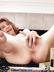 Smiley mature brunette with big tits getting nude and playing with herself