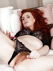 Graceful redhead MILF getting nude and vibing her clit on the bed