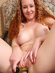 Curly-haired MILF with big jugs pleasing her twat with a gold vibrator