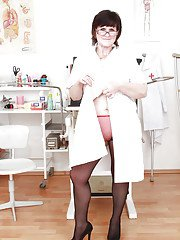 Fatty mature nurse in stockings exposing and fingering her twat in close up