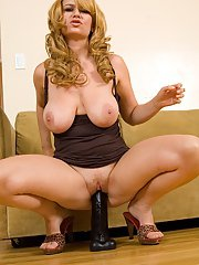 Full-bosomed blonde MILF on high heels playing with a huge black dildo