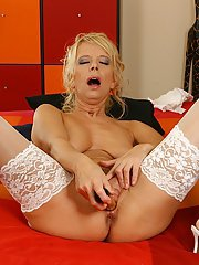 Foxy blondie in white stockings playing with a big gold vibrator