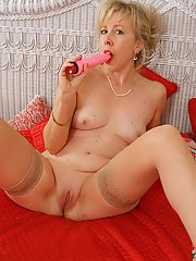 Mature blonde lady in stockings pleasing her shaved cunt with a vibrator