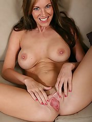 Frisky MILF with round boobies undressing and toying her pink cunt