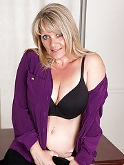 Sassy mature blonde undressing and teasing her gash at her work place