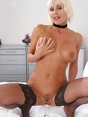 Hot busty blonde MILF in black stockings playing with a glass sex toy