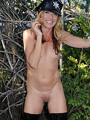 Naughty police lady in sexy uniform undressing and spreading her legs outdoor