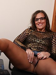Playful mature chick in glasses getting rid of her clothes