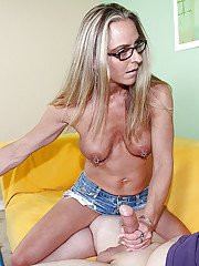 Well-toned mature slut in glasses gives a handjob and receives frontal bukkake