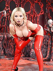 Lusty blonde in latex fetish outfit revealing her big jugs and inviting cunt