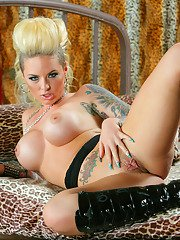 Tattooed knockout revealing her round boobies and inviting pussy