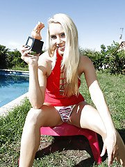 Smiley blonde vixen takes off her red dress and exposes her round jugs