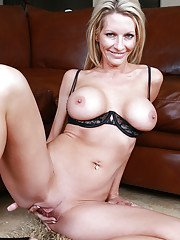 Smiley blonde MILF revealing her round tits and inviting pussy