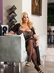 Top-heavy blonde MILF undressing and spreading her nylon clad legs