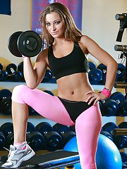 Foxy babe in sport outfit uncovering her luscious curves in the gym