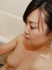 Lusty asian MILF gives a soapy hand and a wet blowjob in the bath