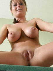 Well-stacked MILF getting naked and exposing her shaved cunt