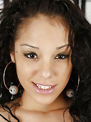 Curly-haired latina sugar in gown and lingerie uncovering her petite curves