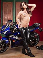 Stunning biker girl slowly uncovering her goods by the muscular motorcycle