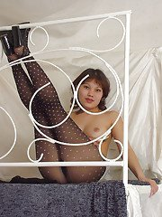 Sassy thai chick in pantyhose and lingerie top revealing her bosoms