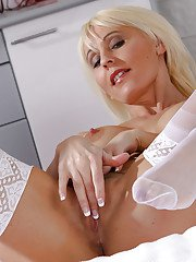 Mature fair-haired whore in stockings masturbates passionately