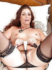 Perky MILF in nylons and lingerie getting nude and playing with a vibrator