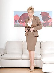 Sassy mature vixen in dress clothes revealing her round boobs and shaved slit