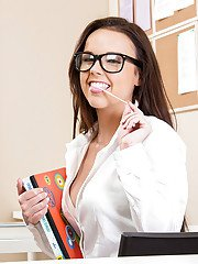 Perky coed in glasses revealing her goods up against a chalkboard
