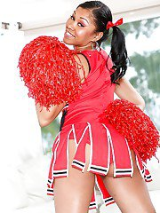 Ebony cheerleader babe poses gorgeously in her sexy red outfit