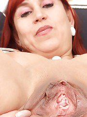 Mature redhead nurse Darja takes off uniform and spreads her pussy