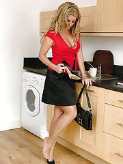 Busty babe with astounding legs Kathryn is posing in her kitchen