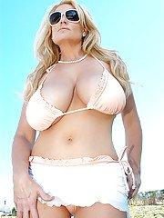 Big tits milf Kelly Madison poses in her white bikini at the pool