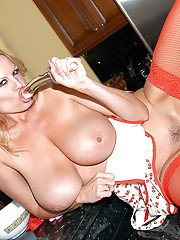 Milf amateur Kelly Madison poses in her sexy red stockings and high heels
