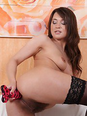Stunning brunette babe Beth teases her hairy pussy in stockings